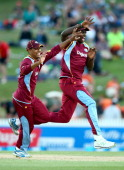 Jason Holder of the West Indies celebrates his runout of Kyle Mills of New Zealand with Kieran Powell during game five of the One Day International...