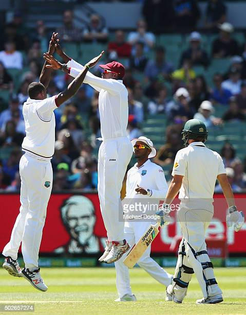 Jason Holder of the West Indies celebrates his wicket of Joe Burns of Australia with Carlos Brathwaite during day three of the Second Test match...