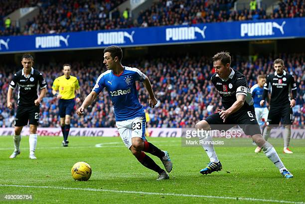 Jason Holt of Rangers is tracked by Christopher Higgins of Queen of the South during the Scottish Championship match between Glasgow Rangers FC and...