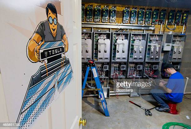 Jason Hughes works on running electoral wiring to junction boxes that are used to convert captured solar energy and store that energy into the Tesla...