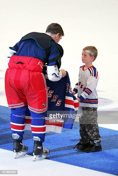 Jason Immonen of the New York Rangers gives his game jersey to a lucky fan after their game against the Ottawa Senators as part of a fan appreciation...