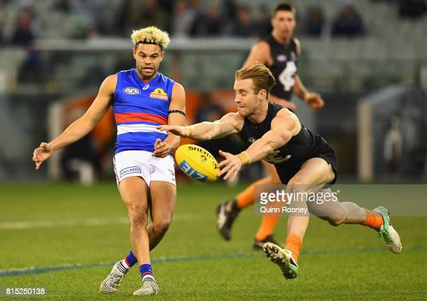 Jason Johannisen of the Bulldogs has his kick smouthered by Nick Graham of the Blues during the round 17 AFL match between the Carlton Blues and the...