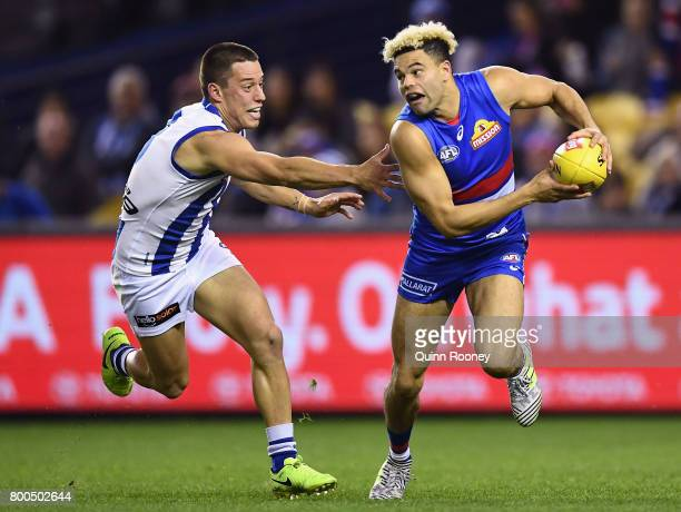 Jason Johannisen of the Bulldogs is chased by Nathan Hrovat of the Kangaroos during the round 14 AFL match between the Western Bulldogs and the North...
