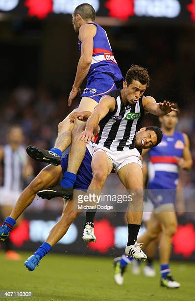 Jason Johannisen of the Bulldogs is hit hard by teamate Jarrad Grant of the Bulldogs in a contest with Jamie Elliott of the Magpies during the NAB...