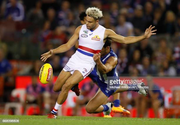 Jason Johannisen of the Bulldogs is tackled by Robbie Tarrant of the Kangaroos during the 2017 AFL round 04 match between the North Melbourne...