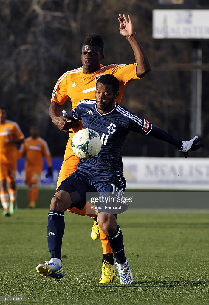 Jason Johnson #14 of the Houston Dynamo and Carlyle Mitchell #19 of the Vancouver Whitecaps FC battle for the ball during the first half of a game on February 20, 2013 in Charleston, North Carolina.