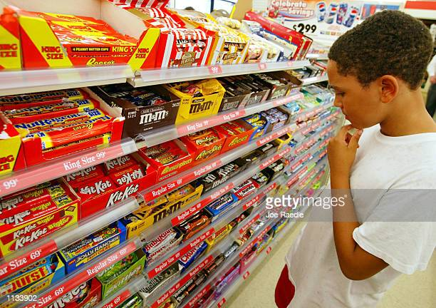 Jason Johnson ponders his choices of candy at a 7Eleven store on July 18 2002 in Pembroke Pines Florida 7Eleven Inc the premiere name and largest...