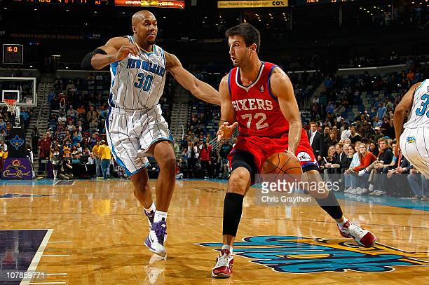 Jason Kapono of the Philadelphia 76ers moves the ball against David West of the New Orleans Hornets at New Orleans Arena on January 3 2011 in New...