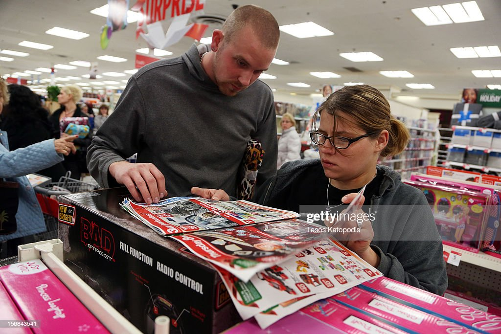 Jason Kettwig (L) and Heather Kettwig of Griffith, Indiana loks through sale papers at a Kmart on Thanksgiving night November 22, 2012 in Griffith, Indiana. City. Many stores got a head start on the traditional Black Friday sales by opening on Thanksgiving.