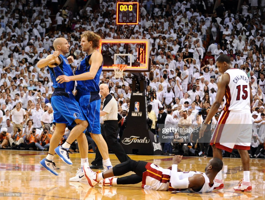 Jason Kidd and Dirk Nowitzki of the Dallas Mavericks celebrate as Dwyane Wade of the Miami Heat lays on the court after missing a lastsecond shot as...