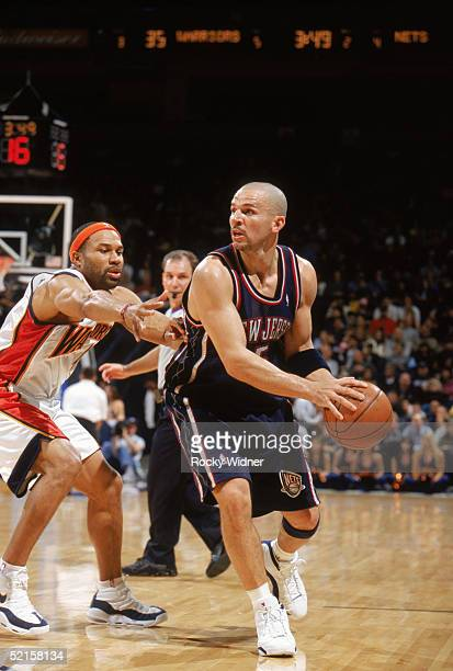 Jason Kidd of the New Jersey Nets looks to move the ball against Derek Fisher of the Golden State Warriors during the game at The Arena in Oakland on...