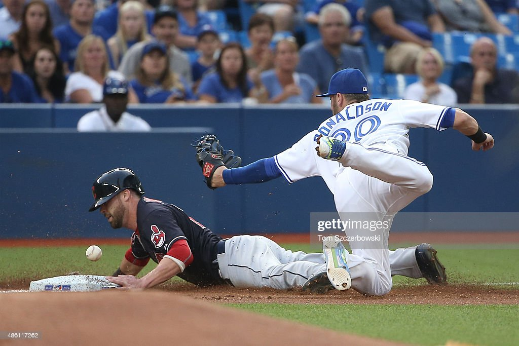 Jason Kipnis of the Cleveland Indians advances safely to third base on a fielder's choice in the first inning during MLB game action as Josh...