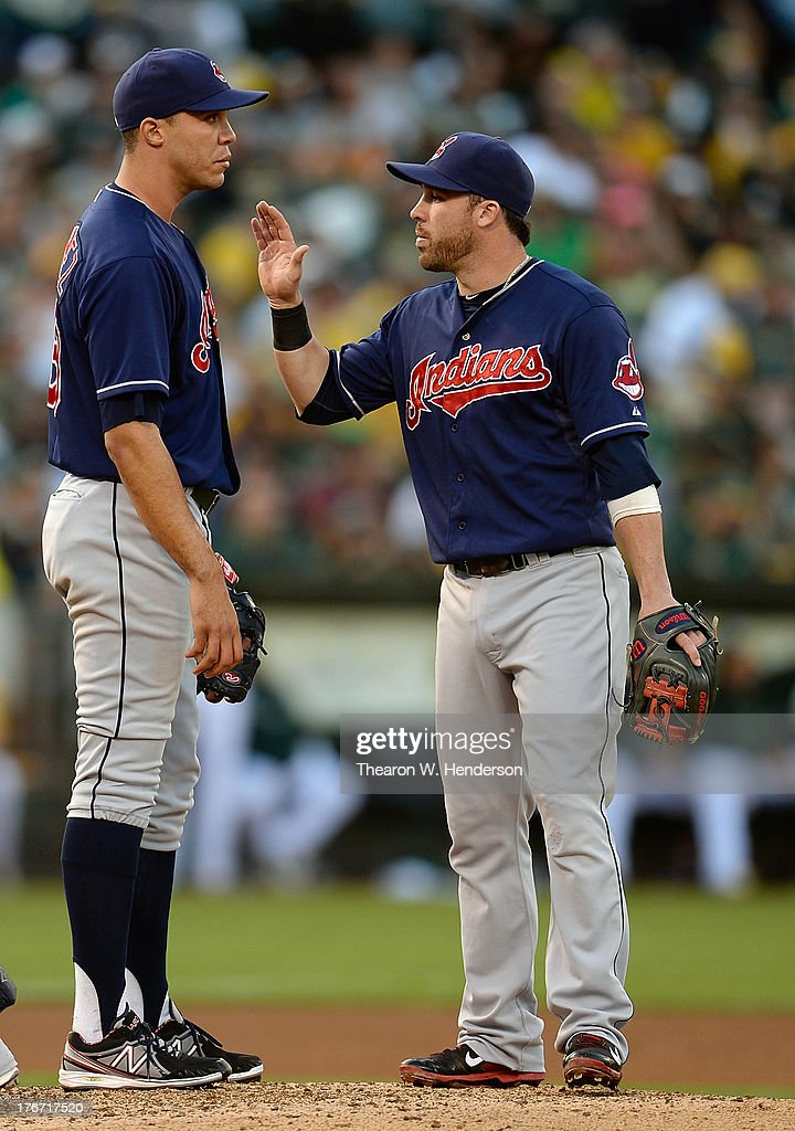 <a gi-track='captionPersonalityLinkClicked' href=/galleries/search?phrase=Jason+Kipnis&family=editorial&specificpeople=5330784 ng-click='$event.stopPropagation()'>Jason Kipnis</a> #22 of the Cleveland Indians comes to the mound to talk with pitcher <a gi-track='captionPersonalityLinkClicked' href=/galleries/search?phrase=Ubaldo+Jimenez&family=editorial&specificpeople=2539590 ng-click='$event.stopPropagation()'>Ubaldo Jimenez</a> #30 after Jimenez walked two runners in the fourth inning against the Oakland Athletics at O.co Coliseum on August 17, 2013 in Oakland, California.