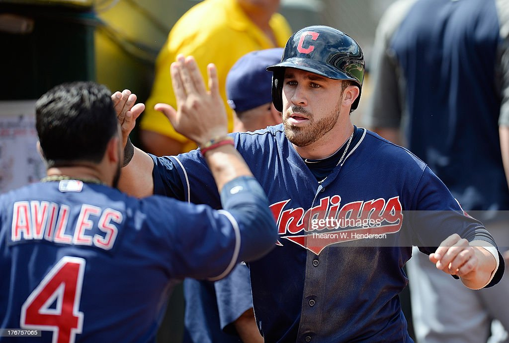 <a gi-track='captionPersonalityLinkClicked' href=/galleries/search?phrase=Jason+Kipnis&family=editorial&specificpeople=5330784 ng-click='$event.stopPropagation()'>Jason Kipnis</a> #22 of the Cleveland Indians is congratulated by <a gi-track='captionPersonalityLinkClicked' href=/galleries/search?phrase=Mike+Aviles&family=editorial&specificpeople=4944765 ng-click='$event.stopPropagation()'>Mike Aviles</a> #4 after Kipnis scored in the fifth inning against the Oakland Athletics at O.co Coliseum on August 18, 2013 in Oakland, California.