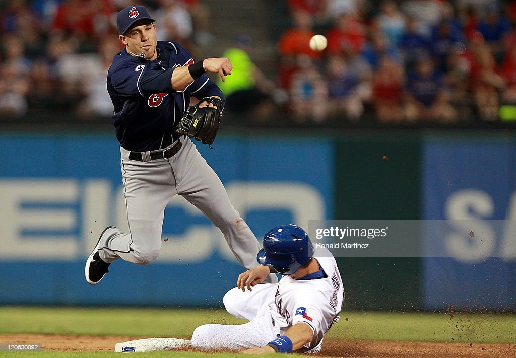 Jason Kipnis of the Cleveland Indians makes the double play against Michael Young of the Texas Rangers and Nelson Cruz at Rangers Ballpark in...