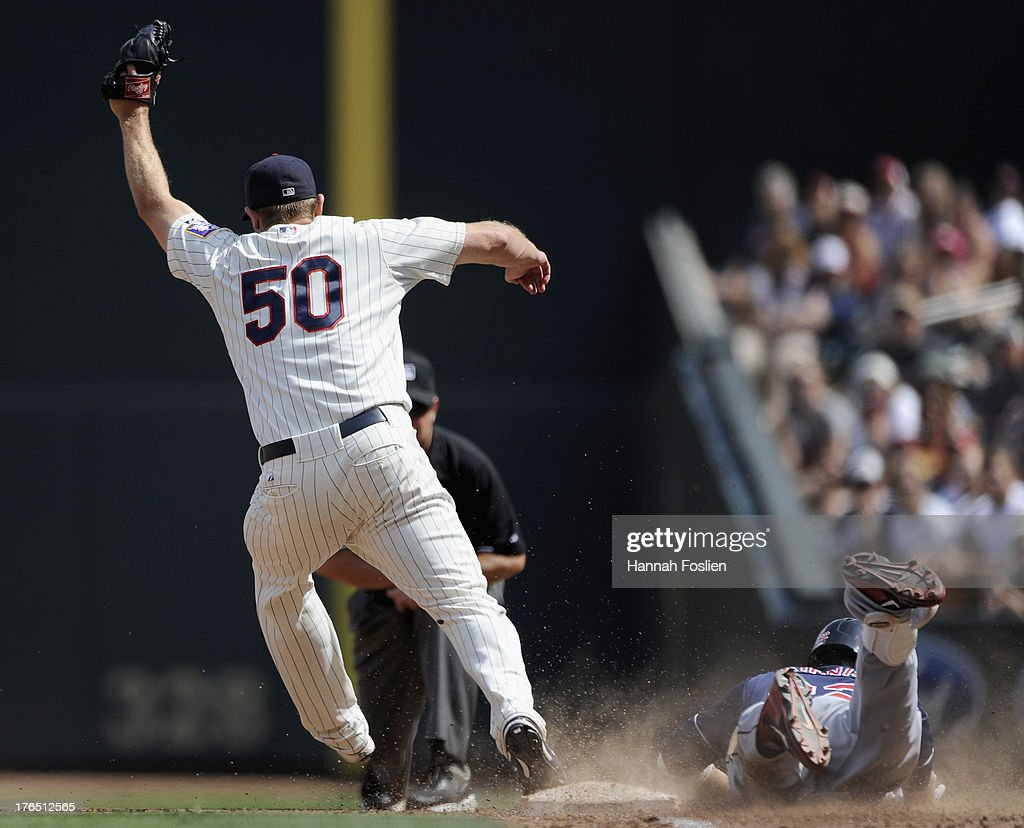 <a gi-track='captionPersonalityLinkClicked' href=/galleries/search?phrase=Jason+Kipnis&family=editorial&specificpeople=5330784 ng-click='$event.stopPropagation()'>Jason Kipnis</a> #22 of the Cleveland Indians slides in safely at first base as Casey Fien #50 of the Minnesota Twins fields the ball during the seventh inning of the game on August 14, 2013 at Target Field in Minneapolis, Minnesota.