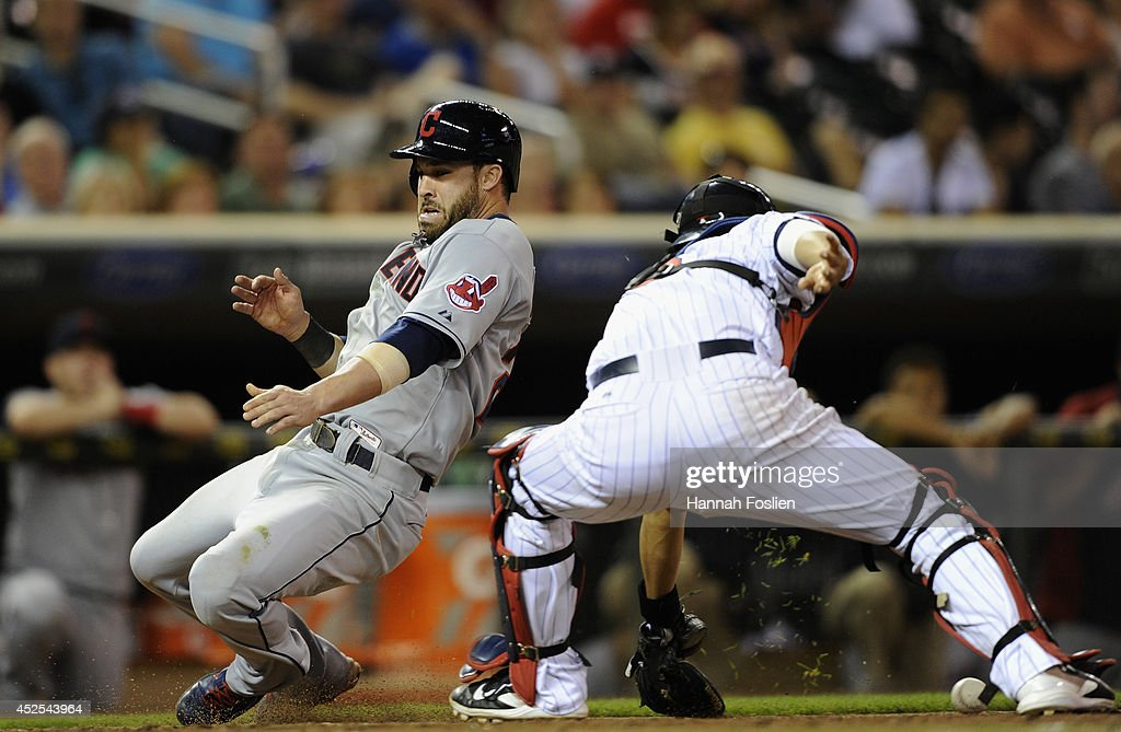 Jason Kipnis of the Cleveland Indians slides safely into home plate as Kurt Suzuki of the Minnesota Twins fields the ball during the ninth inning of...