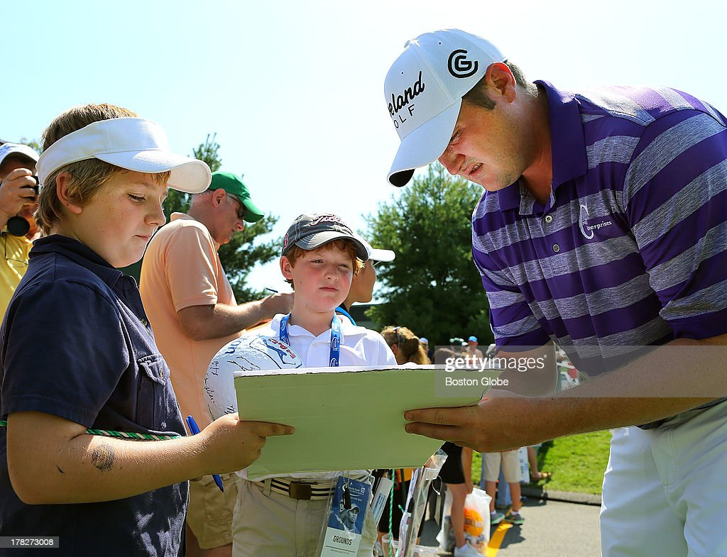 Jason Kokrak signs autographs for Jason Neves, 10, from Dartmouth, left; and Brett Butler, 10, from Wakefield; at the driving range. Practice took place at the TPC Boston for the Deutsche Bank Championship, Aug. 28, 2013.