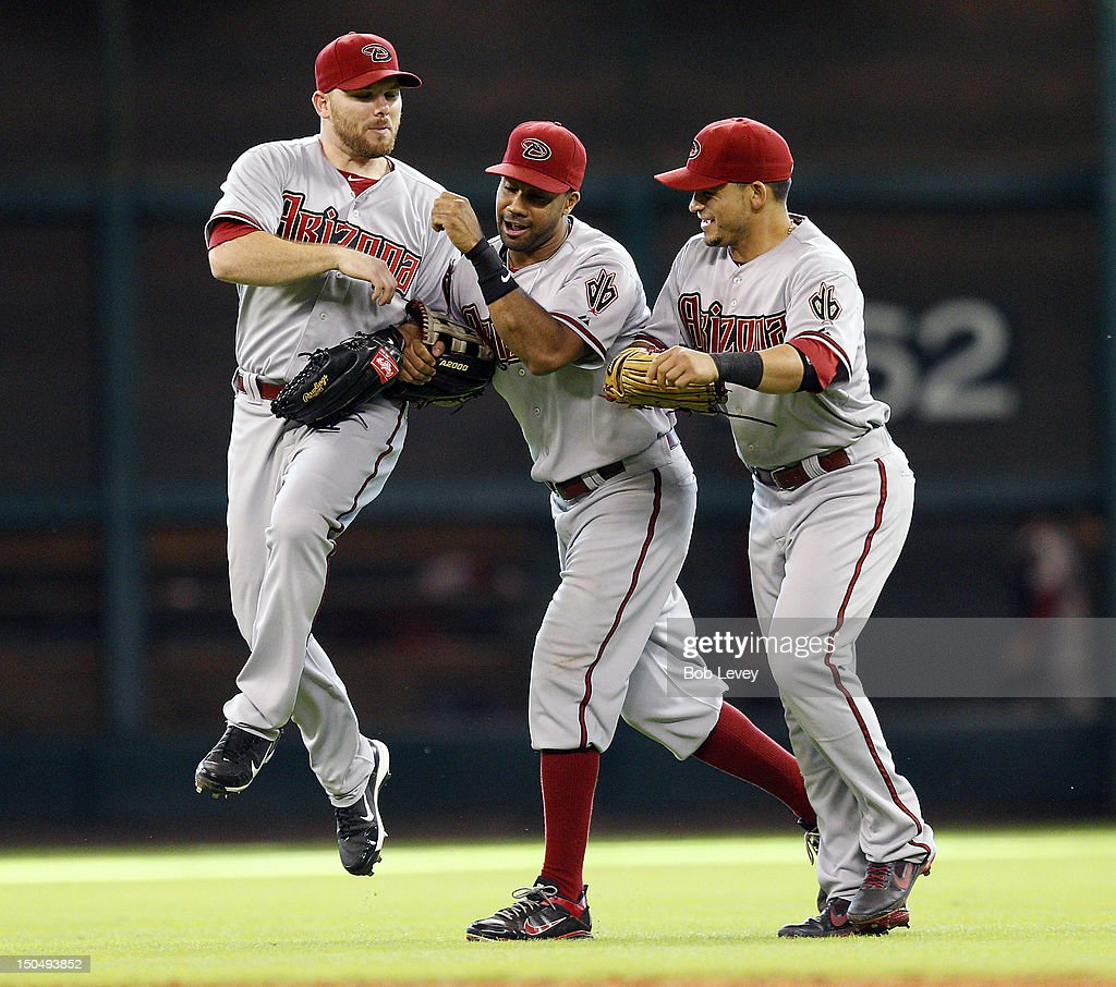 Jason Kubel #13, Chris Young #24 and Gerardo Parra #8 of the Arizona Diamondbacks celebrate after the final out against the Houston Astros at Minute Maid Park on August 19, 2012 in Houston, Texas.