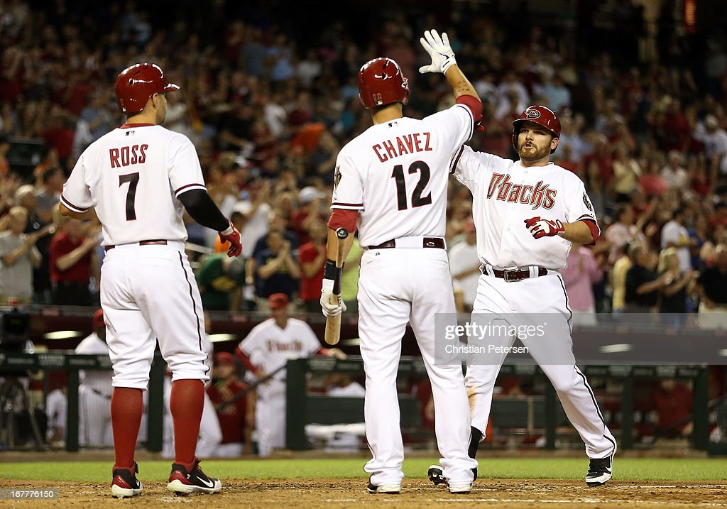 Jason Kubel #13 (R) of the Arizona Diamondbacks high-fives Cody Ross #7 and Eric Chavez #12 after hitting a two-run home run against the San Francisco Giants during the fourth inning of the MLB game at Chase Field on April 29, 2013 in Phoenix, Arizona.