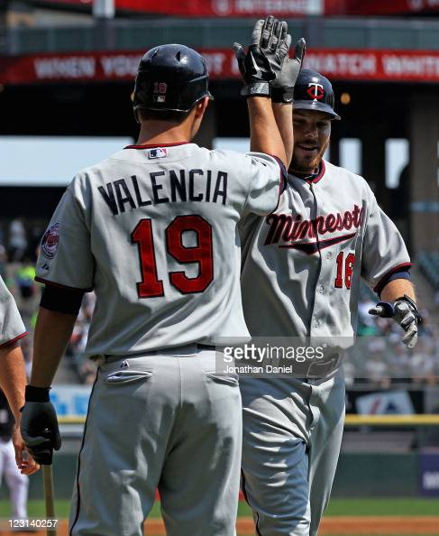 Jason Kubel of the Minnesota Twins is greeted by teammate Danny Valencia after hitting a tworun home run in the 1st inning against the Chicago White...