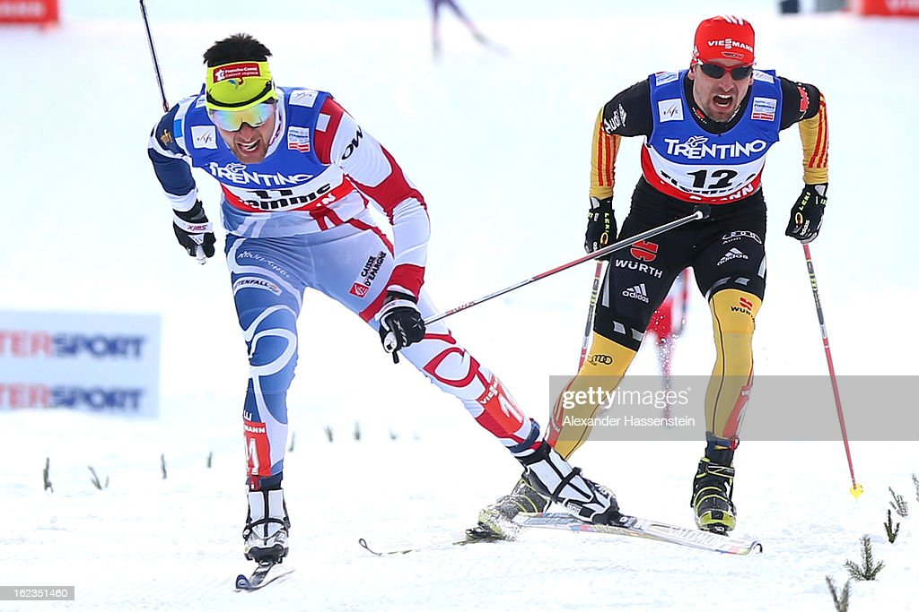 Jason Lamy Chappuis (L) of France crosses the finish line ahead of Bjoern Kircheisen (R) of Germany, who wons the 3rd place of the Men's Nordic Combined on February 22, 2013 in Val di Fiemme, Italy.