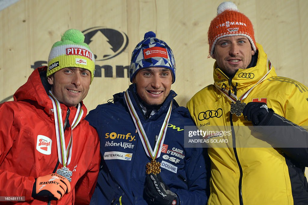 Jason Lamy Chappuis (C) poses on February 23, 2013 with his gold medal next to second-placed Austrian Mario Stecher (L) and third-placed German Bjoern Kircheisen on the podium of the individual men's nordic combined NH event of the FIS Nordic World Ski Championships in Cavalese.