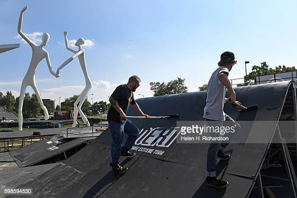 Jason Lorenz right and Alex Bingham middle use rollers to paint platforms for the BMX and skateboard structures to be used for the upcoming FISE...