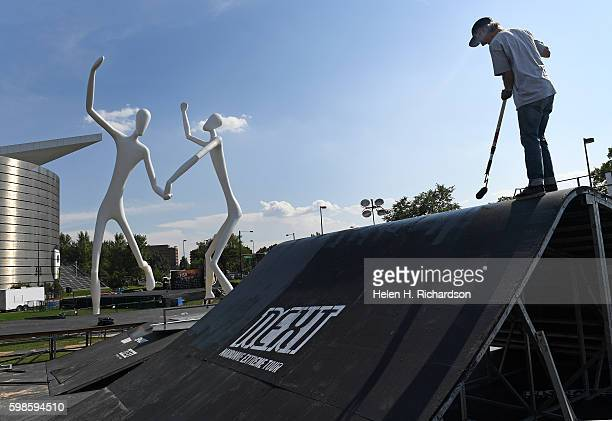 Jason Lorenz right uses rollers to paint platforms for the BMX and skateboard structures to be used for the upcoming FISE Sculpture Park Festival on...