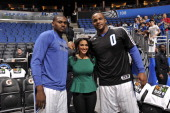 Jason Maxiell and Glen Davis of the Orlando Magic pose with a fan before the game against the Charlotte Bobcats on January 19 2014 at Amway Center in...