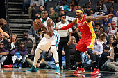 Jason Maxiell of the Charlotte Hornets posts up against Josh Smith of the Houston Rockets during the game at the Time Warner Cable Arena on April 13...