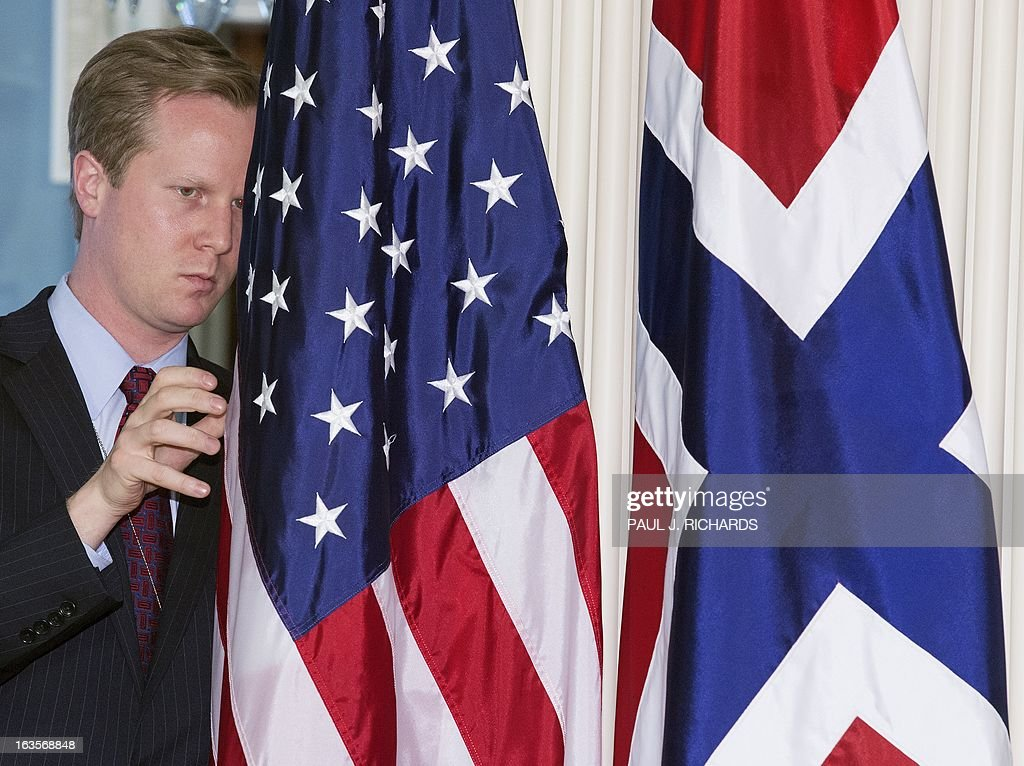 Jason Meininger, Aide to US Secretary of State John Kerry, adjusts the flags shortly before the arrival of Norwegian Foreign Minister Espen Barth Eide, at the US Department of State Treaty Room March 12, 2013, in Washington, DC. AFP Photo/Paul J. Richards