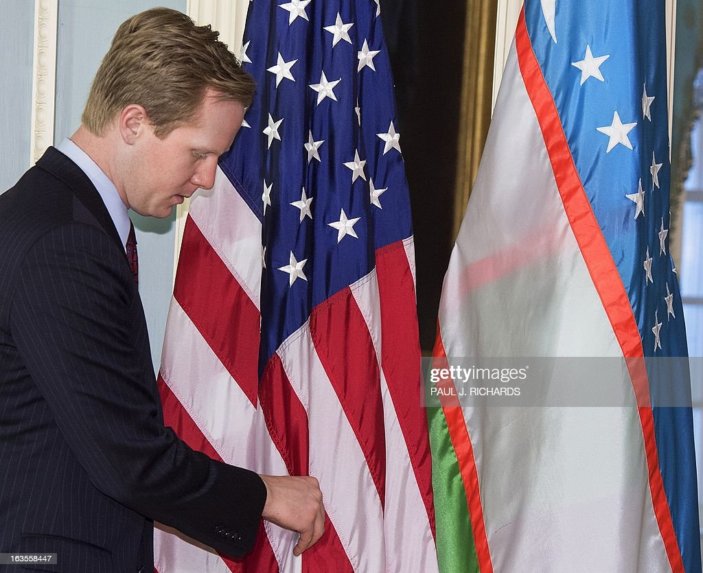 Jason Meininger, the Aide to US Secretary of State John Kerry adjusts the ceremonial flags for the arrival the Foreign Minister of Uzbekistan, Abdulaziz Kamilov, and brief remarks to the media by Kerry and Kamilov, March 12, 2013 after their private bilateral meeting at the State Dept in Washington, DC. AFP Photo/Paul J. Richards