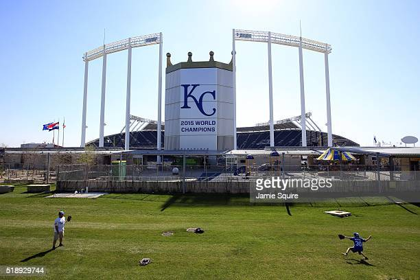 Jason Nealand and son Joshua Nealand of Kansas City Missouri play catch in front of Kauffman Stadium ahead of the Opening Day game between the Kansas...