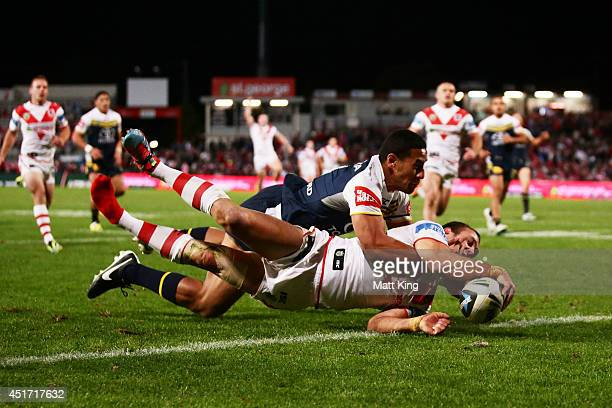 Jason Nightingale of the Dragons beats Tautau Moga of the Cowboys to score a try during the round 17 NRL match between the St George Illawarra...