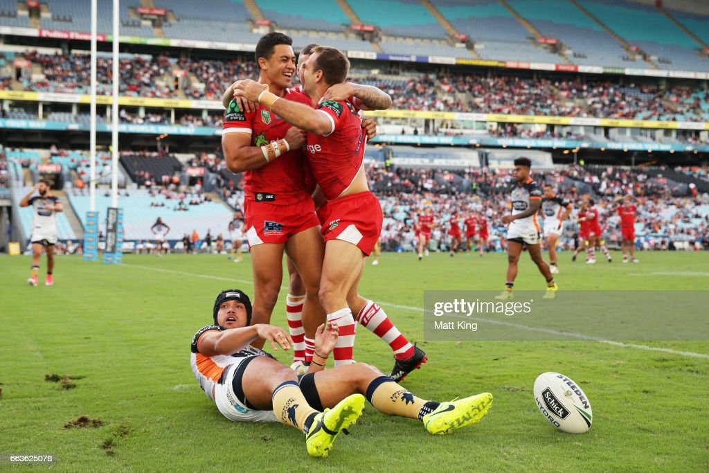 Jason Nightingale of the Dragons celebrates with team mates after scoring a try as David Nofoaluma of the Tigers looks on during the round five NRL match between the Wests Tigers and the St George Illawarra Dragons at ANZ Stadium on April 2, 2017 in Sydney, Australia.