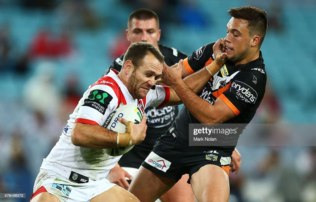 Jason Nightingale of the Dragons palms off Luke Brooks of the Tigers during the round 20 NRL match between the St George Illawarra Dragons and the Wests Tigers at ANZ Stadium on July 24, 2016 in Sydney, Australia.