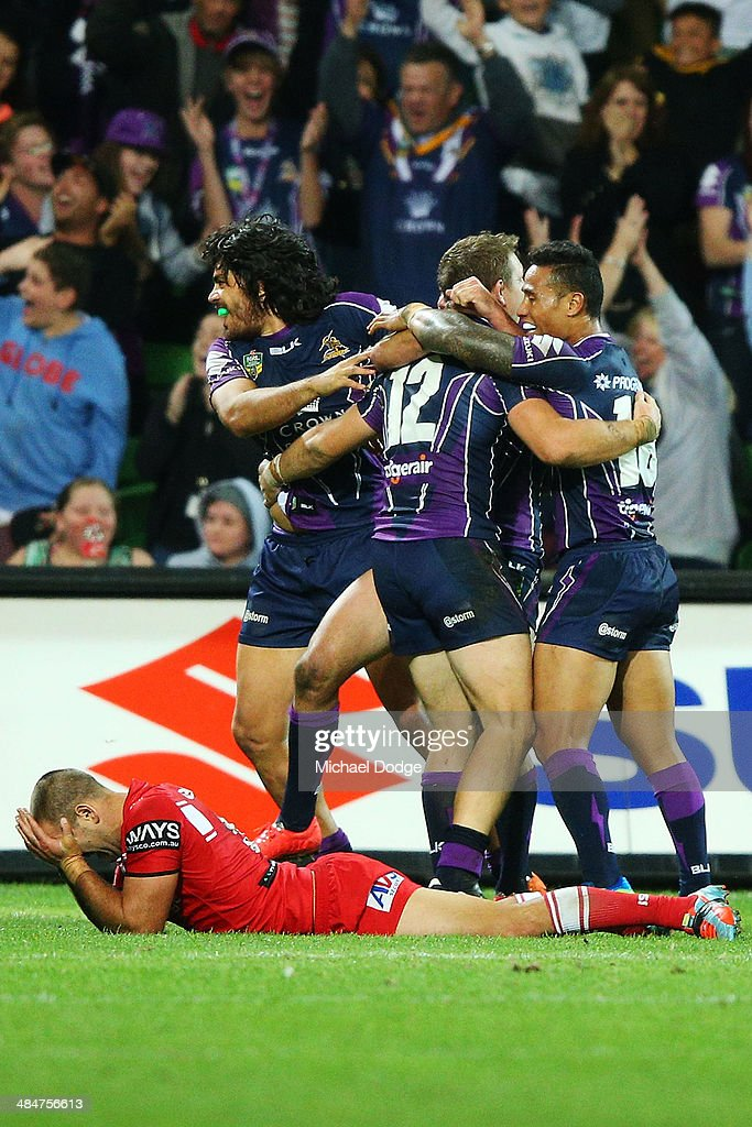 Jason Nightingale of the Dragons reacts as Storm players celebrate their win during the round 6 NRL match between the Melbourne Storm and the St George Illawarra Dragons at AAMI Park on April 14, 2014 in Melbourne, Australia.