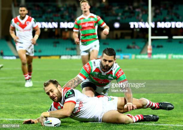 Jason Nightingale of the Dragons scores a try as he avoids a tackle from Adam Reynolds of the Rabbitohs during the round 22 NRL match between the St...