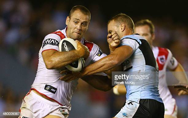 Jason Nightingale of the Sharks is tackled by Daniel Holdsworth during the round three NRL match between the CronullaSutherland Sharks and the St...