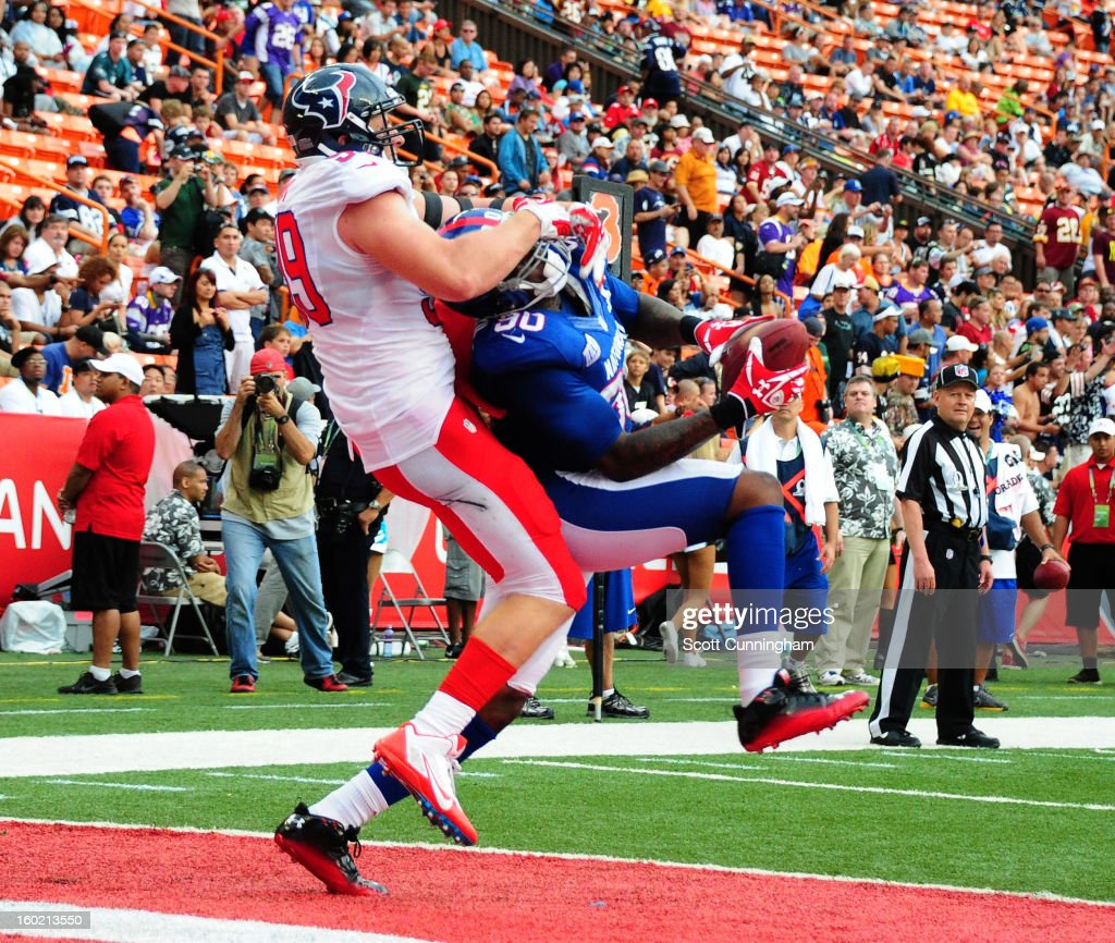 Jason Pierre-Paul #90 of the New York Giants and the NFC intercepts a pass against J. J. Watt #90 of the American Football Conference team during the 2013 Pro Bowl at Aloha Stadium on January 27, 2013 in Honolulu, Hawaii