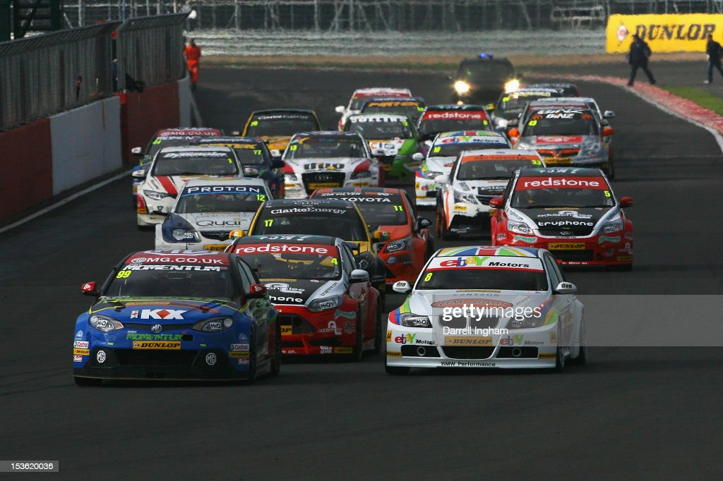 Jason Plato of Great Britain drives the #99 MG KX Momentum Racing MG6 ahead of #8 Rob Collard and the field at the start of the Dunlop MSA British Touring Car Championship race at the Silverstone Circuit on October 7, 2012 in Towcester, United Kingdom.