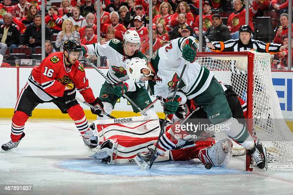 Jason Pominville and Mikael Granlund of the Minnesota Wild watch as goalie Corey Crawford of the Chicago Blackhawks attempts to stop the puck which...