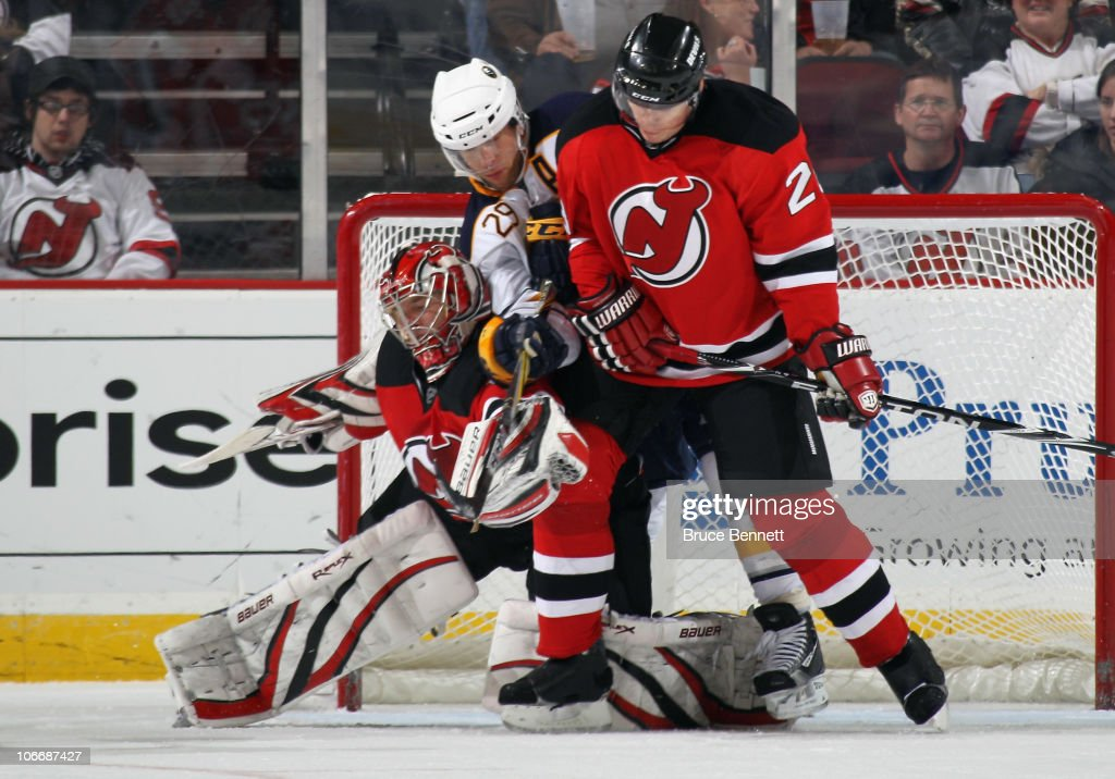 Jason Pominville of the Buffalo Sabres looks to deflect the puck in front of goaltender Johan Hedberg and Anton Volchenkov of the New Jersey Devils...