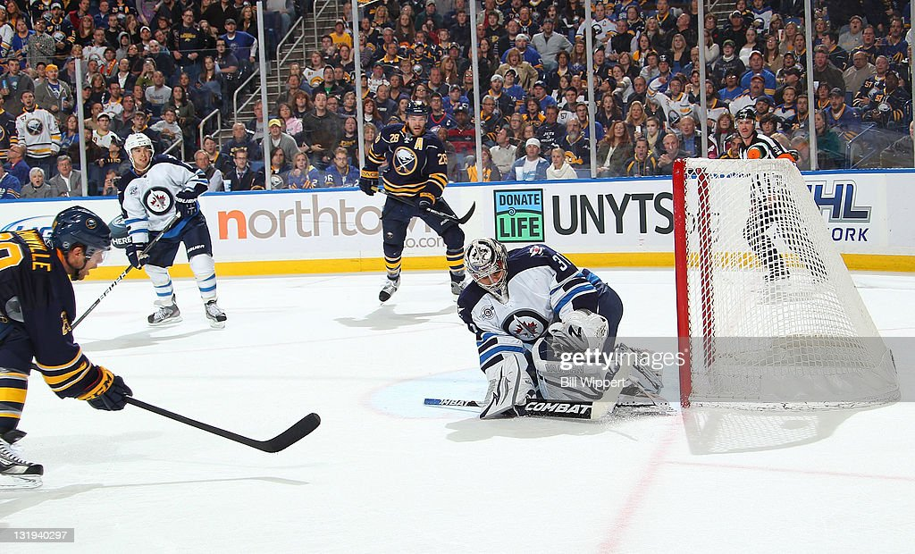 <a gi-track='captionPersonalityLinkClicked' href=/galleries/search?phrase=Jason+Pominville&family=editorial&specificpeople=570525 ng-click='$event.stopPropagation()'>Jason Pominville</a> #29 of the Buffalo Sabres scores a first period shorthand goal against Ondrej Pavelec #31 of the Winnipeg Jets on a pass from teammate <a gi-track='captionPersonalityLinkClicked' href=/galleries/search?phrase=Paul+Gaustad&family=editorial&specificpeople=577980 ng-click='$event.stopPropagation()'>Paul Gaustad</a> #28 at First Niagara Center on November 8, 2011 in Buffalo, New York.