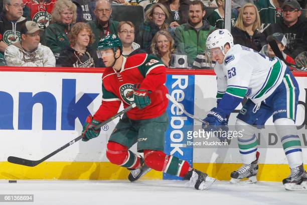 Jason Pominville of the Minnesota Wild controls the puck along the boards with Bo Horvat of the Vancouver Canucks defending during the game on March...