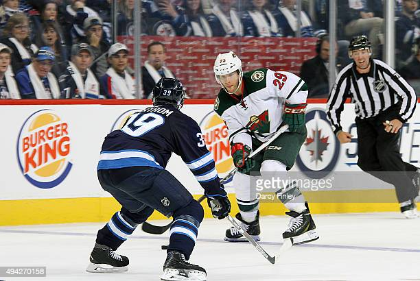 Jason Pominville of the Minnesota Wild plays the puck down the ice as Toby Enstrom of the Winnipeg Jets defends during third period action at the MTS...