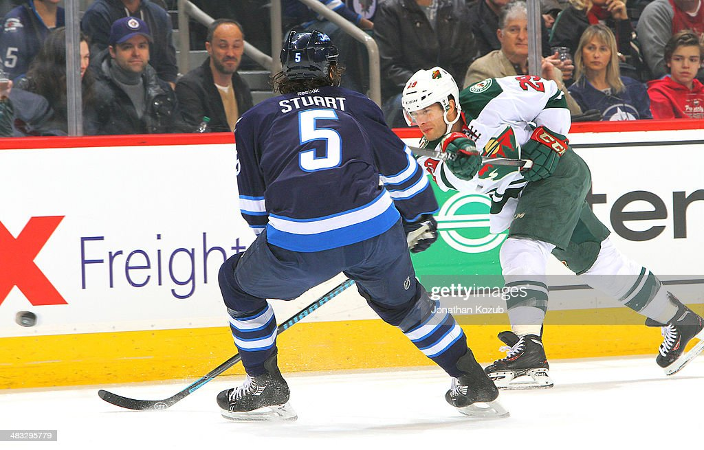 Jason Pominville #29 of the Minnesota Wild shoots the puck past a defending Mark Stuart #5 of the Winnipeg Jets during first period action at the MTS Centre on April 7, 2014 in Winnipeg, Manitoba, Canada.