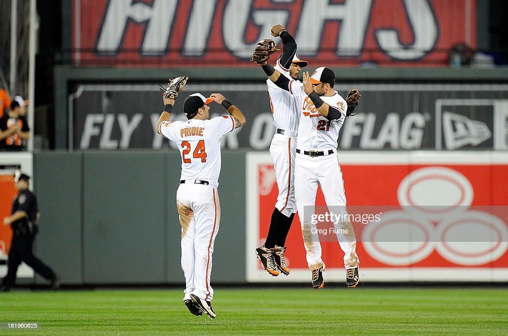 Jason Pridie #24, Adam Jones #10 and Nick Markakis #21 of the Baltimore Orioles celebrate after a 3-2 victory against the Toronto Blue Jays at Oriole Park at Camden Yards on September 26, 2013 in Baltimore, Maryland.