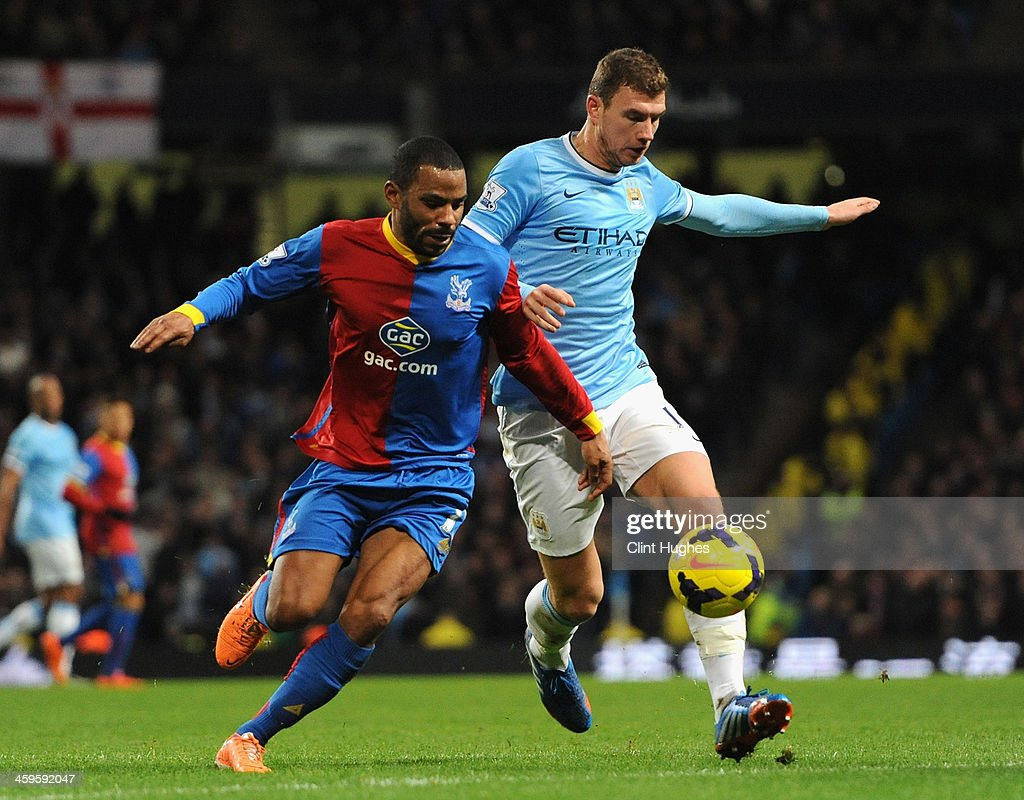 Jason Puncheon of Crystal Palace competes with <a gi-track='captionPersonalityLinkClicked' href=/galleries/search?phrase=Edin+Dzeko&family=editorial&specificpeople=4404455 ng-click='$event.stopPropagation()'>Edin Dzeko</a> of Manchester City during the Barclays Premier League match between Manchester City and Crystal Palace at the Etihad Stadium on December 28, 2013 in Manchester, England.